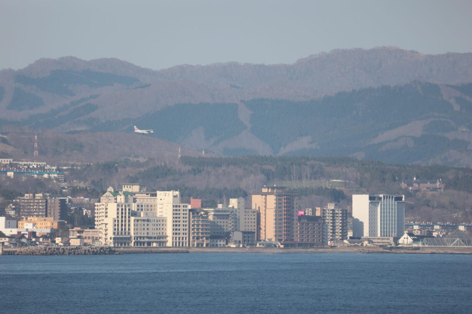 函館市街地を飛ぶ小型プロペラ機の様子